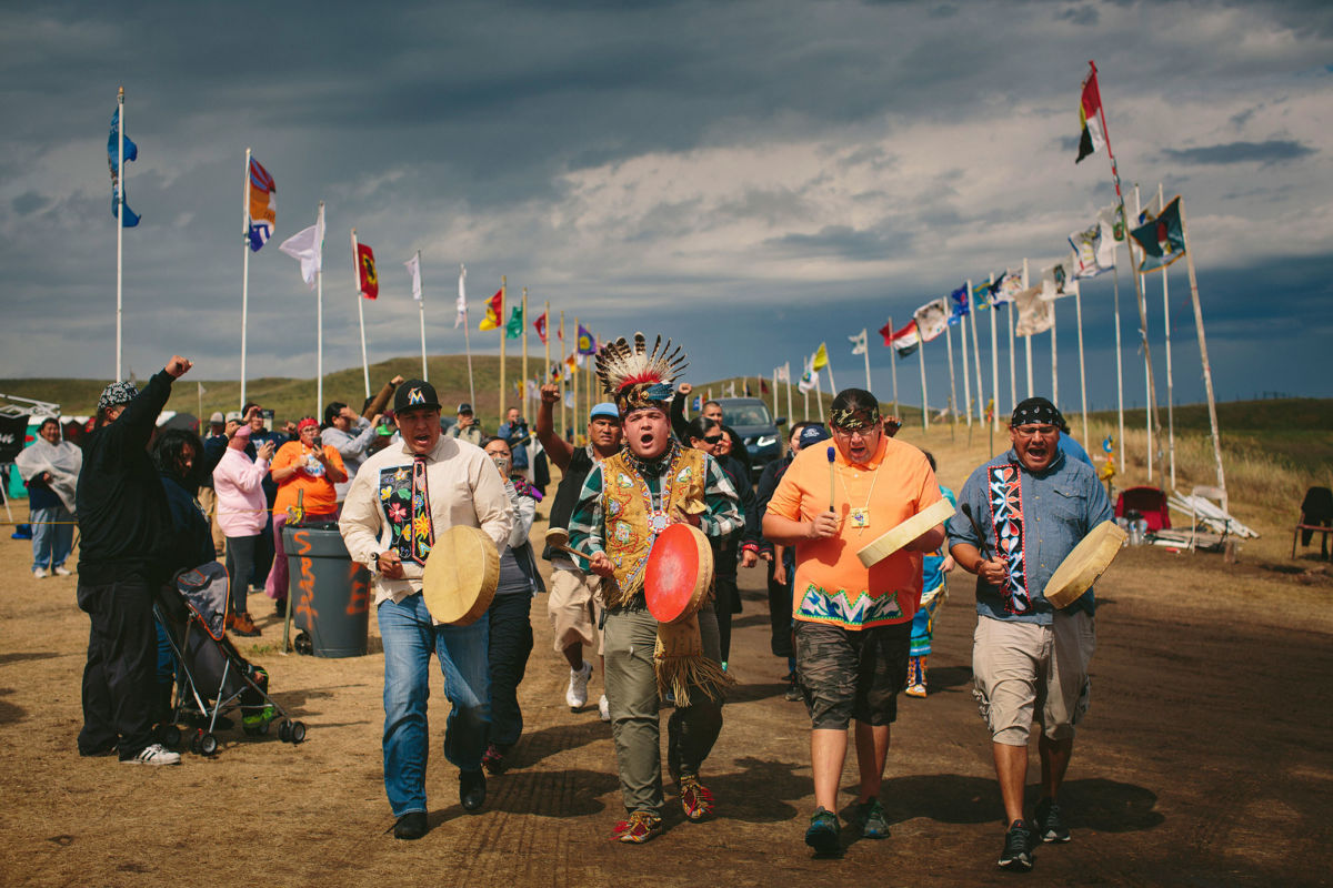 The photo shows four Native men marching at the head of a procession, with flags of many nations behind them.