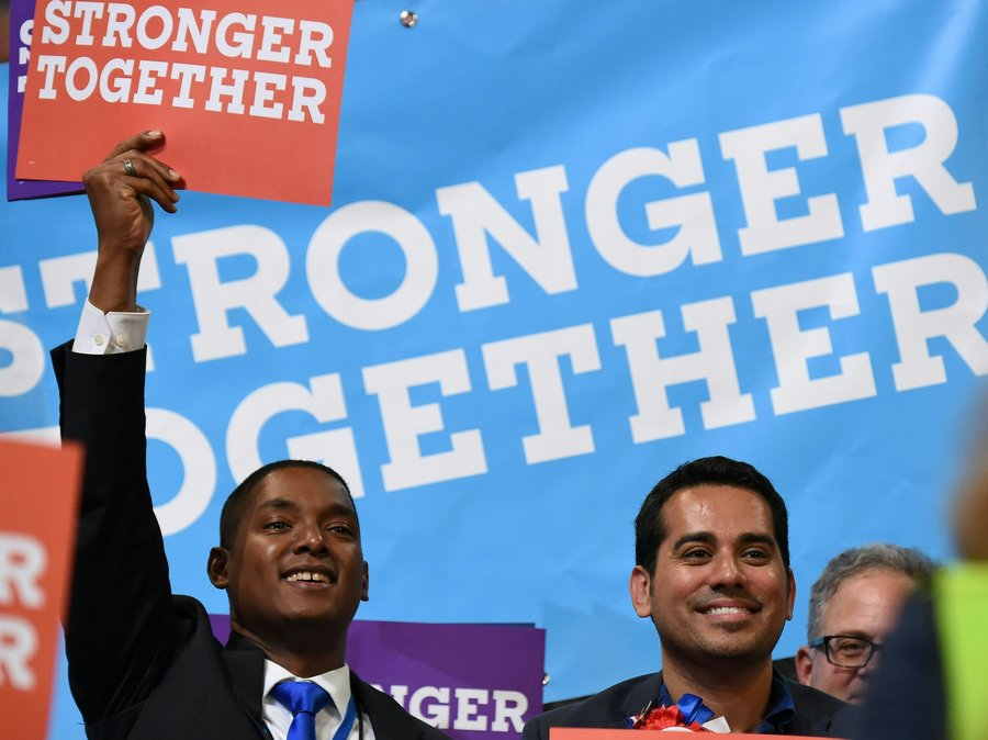 """The photo shows a black man holding a sign that says """"stronger together."""" He's seated next to a man who appears Latino, and a white man."""