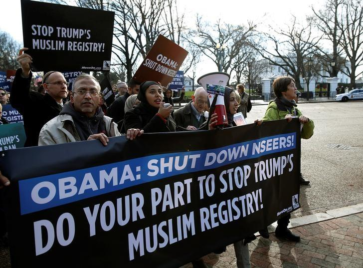 "The image shows people at a protest march, holding a sign which says ""Obama: Shut down NSEERS! Do your part to stop Trump's Muslim registry!"""