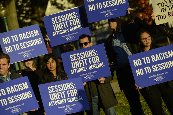 """The photo shows protestors holding signs saying """"No to racism, no to Sessions"""""""