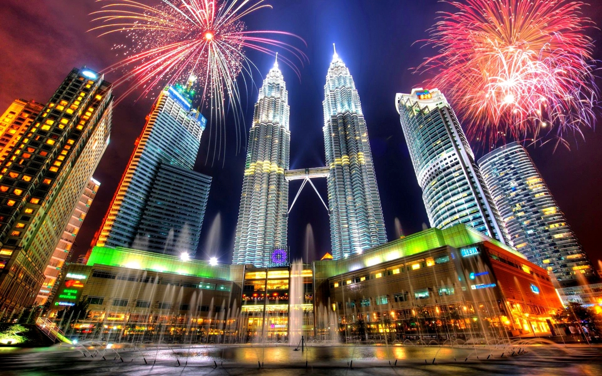 The photo shows buildings in Kuala Lumpur at night, with fireworks exploding overhead