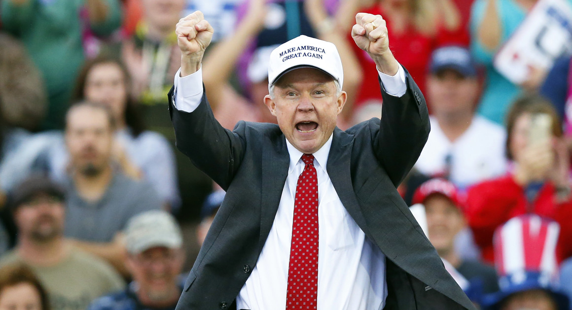 "The image shows Jeff Session, a middle-aged white man in a black suit jacket and ""Make America Great Again"" hat, at a political rally"
