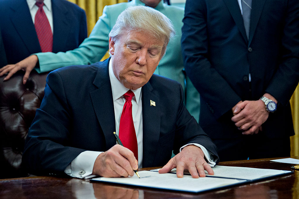 The photo shows Donald Trump signing an executive order.